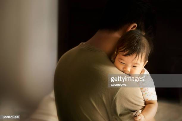 Asian toddler carried by father in moody bedroom background.