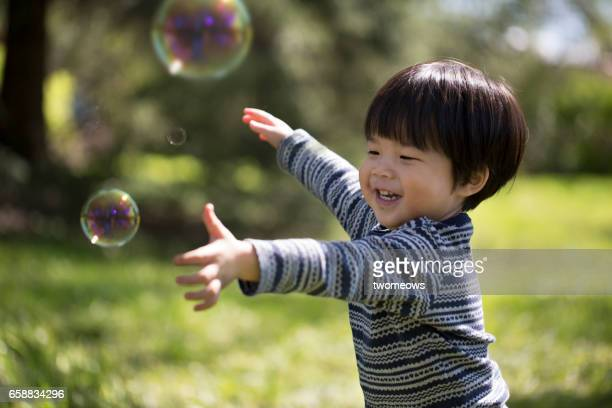 Asian toddler catching soap bubble.