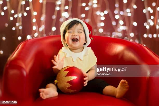 Asian toddler dress as elf on illuminated light bulb background.