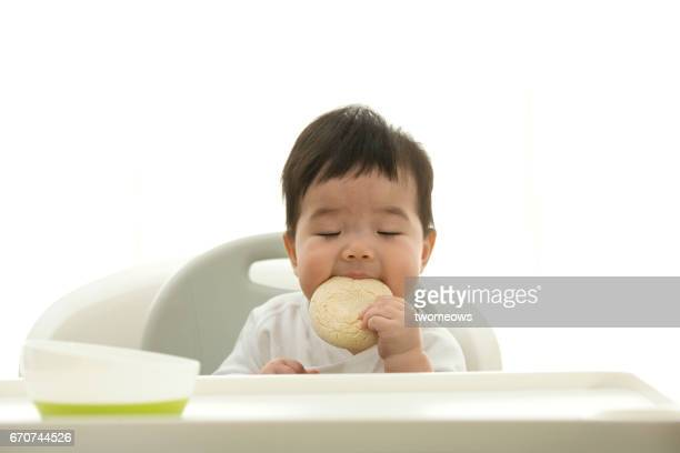 Asian toddler eating baby food cookies.