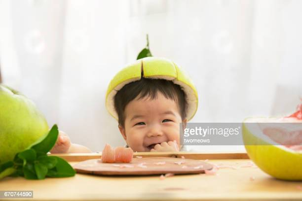 asian toddler eating fruits, looking silly with pomelo skin as a hat. - asian baby stockfoto's en -beelden