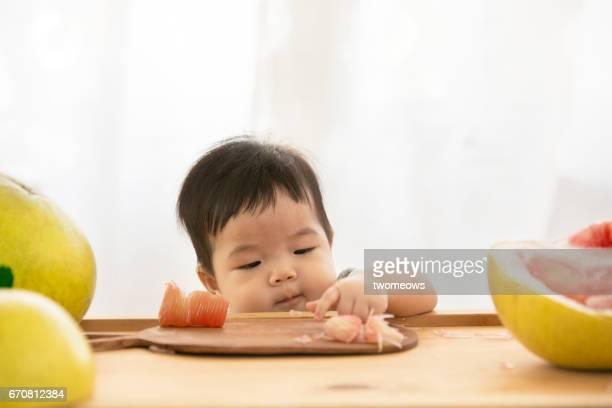 Asian toddler eating pomelo fruit.