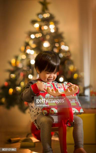 Asian toddler holding a present on Christmas tree background.