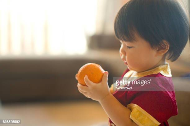 Asian toddler in Chinese traditional clothing Cheongsam, holding tangerine.