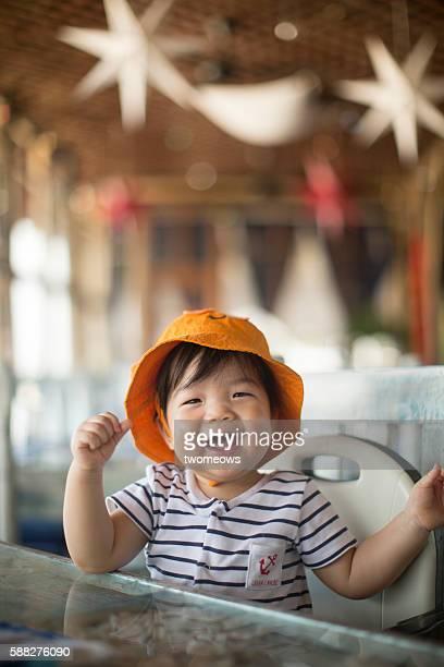 Asian toddler in restaurant.