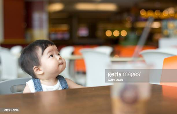 Asian toddler in shopping mall food court.