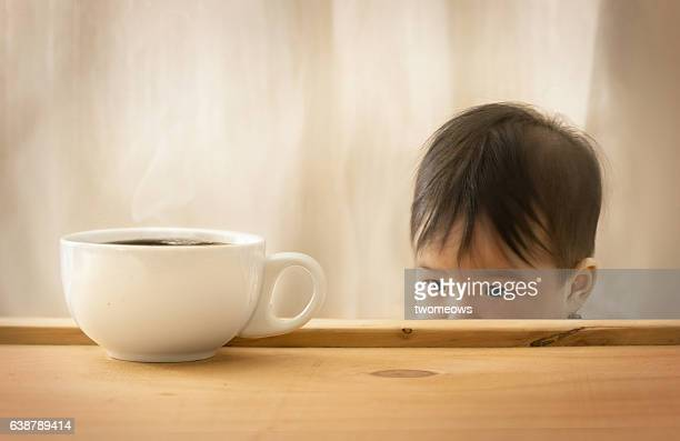 Asian toddler looking at coffee cup.