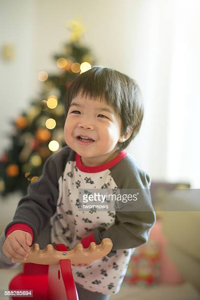 Asian toddler on rocking deer on Christmas tree background.