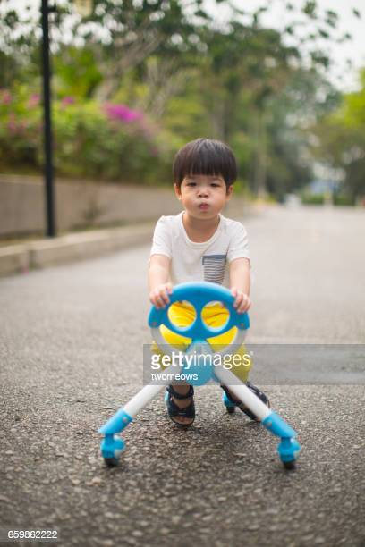 Asian toddler on tricycle.