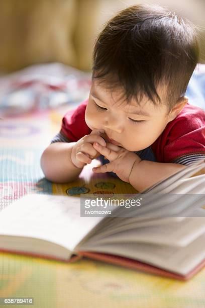 Asian toddler reading a book.