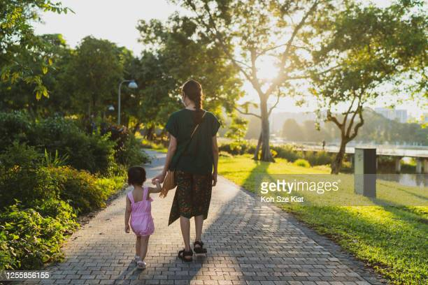 asian toddler taking small steps and holding on to mother's hand for support - singapore stock pictures, royalty-free photos & images