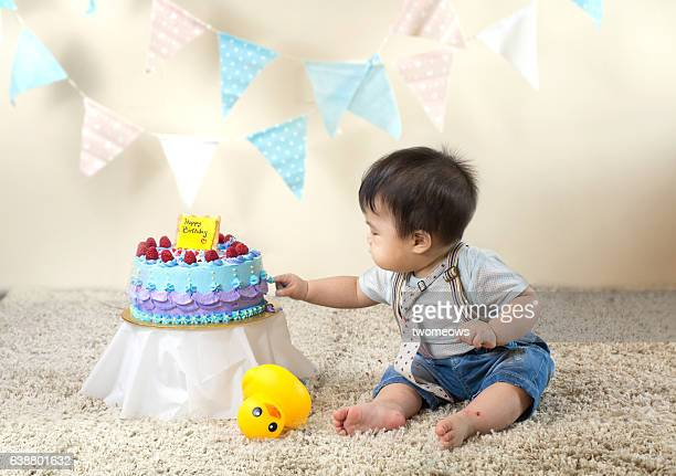 Asian toddler with birthday cake.