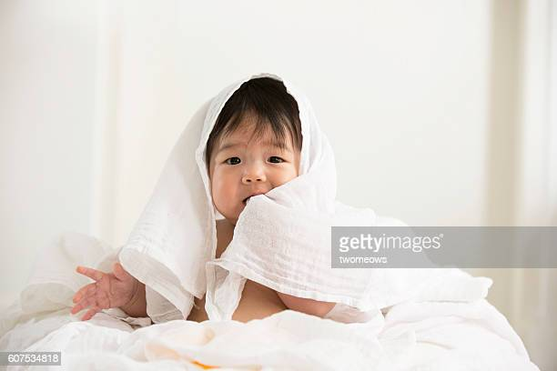 Asian toddler wrapped by white towel.