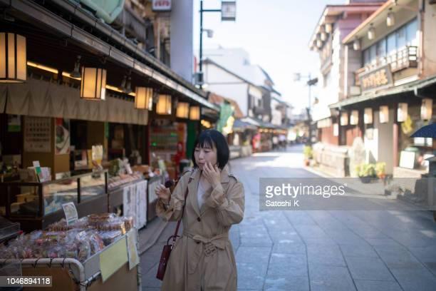 アジア tourinst だんごを食べると古い日本の商店街を歩く - ショッピングエリア ストックフォトと画像
