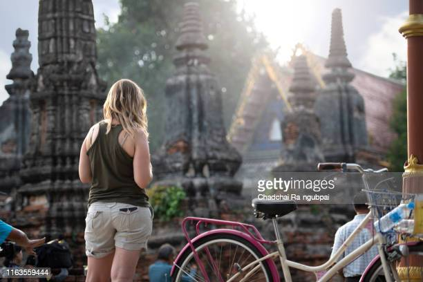 asian tourist and historic sites. women like to travel by bicycle to visit the historic city in thailand. - sukhothai stockfoto's en -beelden