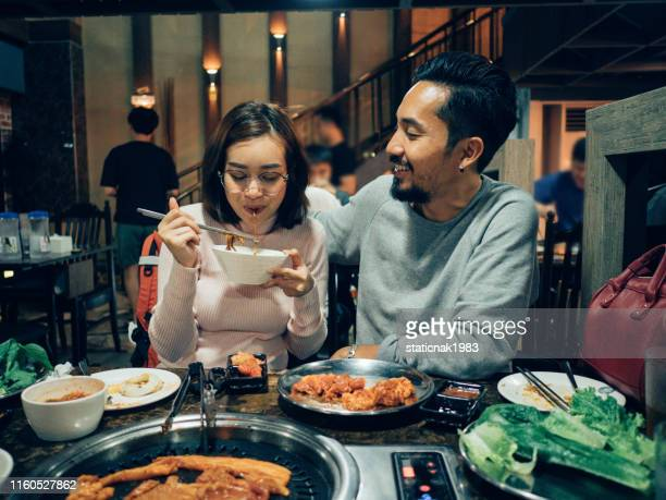 asian tourist couple eating korean barbecue buffet with his daughter in the restaurant. - korean culture stock pictures, royalty-free photos & images