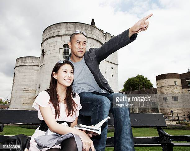 asian tourist couple sitting on bench, looking at map, tower of london in background. london. england uk - hugh sitton stock pictures, royalty-free photos & images