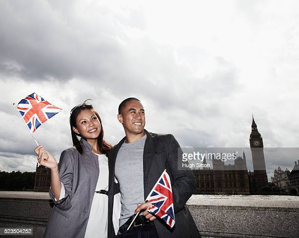 asian tourist couple standing together holding small union jack, london, england, uk - hugh sitton stock pictures, royalty-free photos & images
