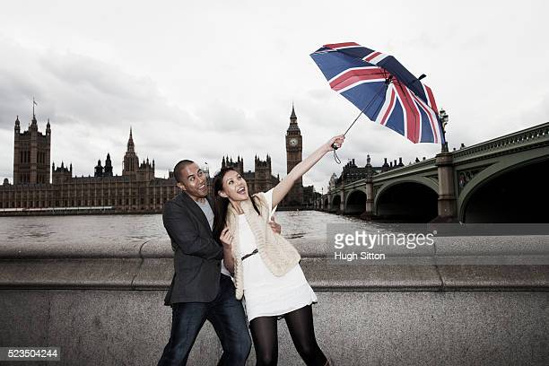 asian tourist couple standing together holding union jack umbrella, london, england, uk - hugh sitton stock pictures, royalty-free photos & images