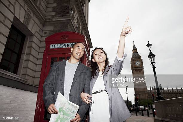 asian tourist couple standing together in front of red telephone box. big ben in background, london, england, uk - hugh sitton stock pictures, royalty-free photos & images