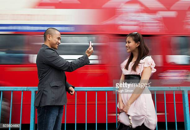 asian tourist couple taking pictures of each other, standing in front of red doubledecker bus passing by. london. england, uk - hugh sitton stock pictures, royalty-free photos & images