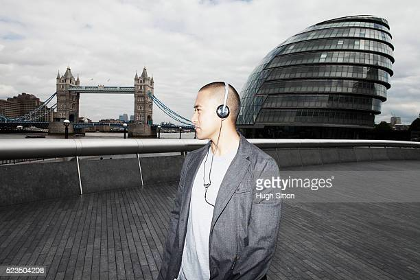 asian tourist listening to music with tower bridge and london city hall in background, london, england uk - hugh sitton stock-fotos und bilder