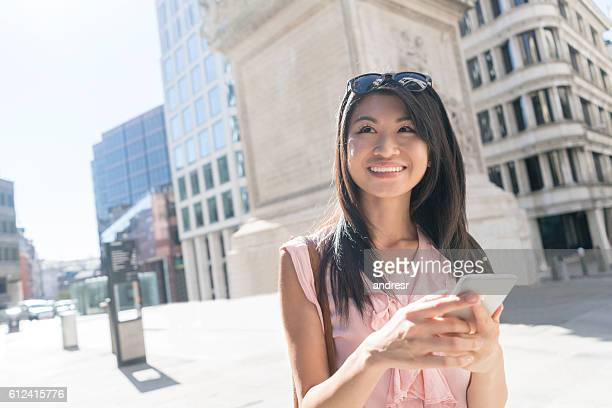 Asian tourist using maps app on a cell phone