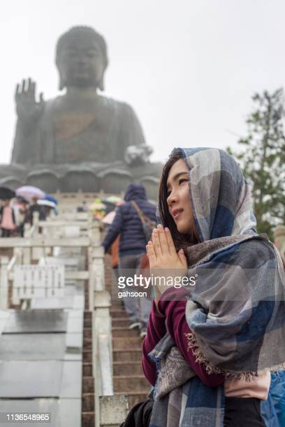 asian tourist visiting tian tan buddha in ngong pinglantau island, hong kong, worshipping in rainny day. the big buddha, is a large bronze statue of buddha shakyamuni, one of the most visited travel destination in hk - religious occupation stock pictures, royalty-free photos & images