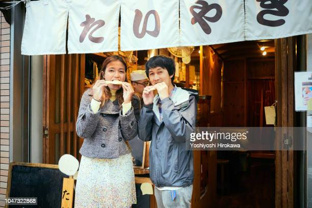 asian tourists eat traditional sweets in japan. - のれん ストックフォトと画像