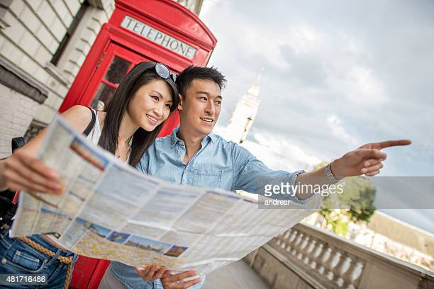 Asian tourists in London holding a map