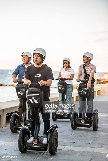 asian tourists on segways in barcelona, spain - segway stock pictures, royalty-free photos & images