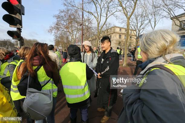 Asian tourists speak with protestors dressed in a yellow overall near the Chateau de Versailles in Versailles outside Paris ahead of a quotYellow...