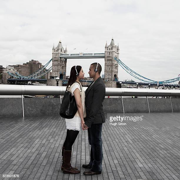 asian tourists standing together, listening to music, with tower bridge in background, london, england, uk - hugh sitton stock pictures, royalty-free photos & images