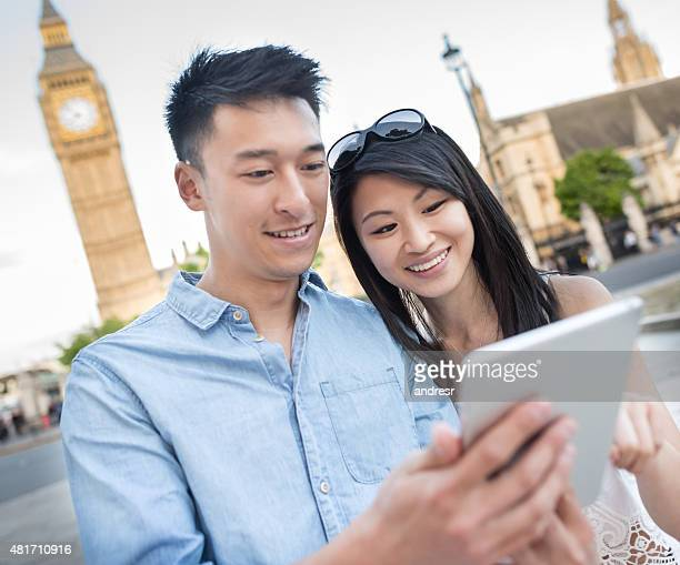 Asian tourists using a tablet in London while traveling