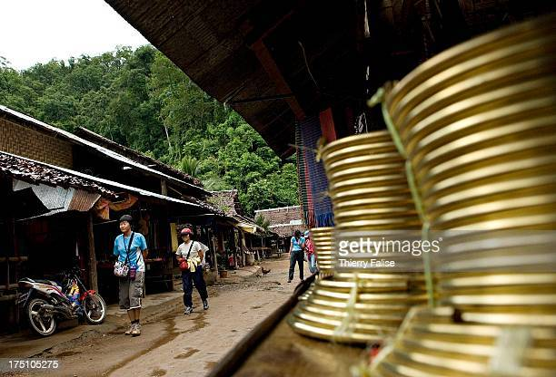Asian tourists walk in the 'long neck' Huay Sua Tao village Northern Thailand The 'long necks' are female ethnic Padaung a subgroup of the Karen...