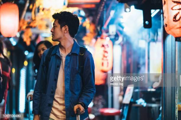 アジアの観光客が夜の路地を歩く - 歓楽街 ストックフォトと画像