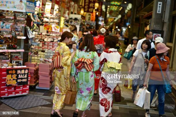 Asian tourists wearing traditional kimonos shopping visiting the Nishiki Market First starting as a fish market in 1615 Nishiki Market is a...