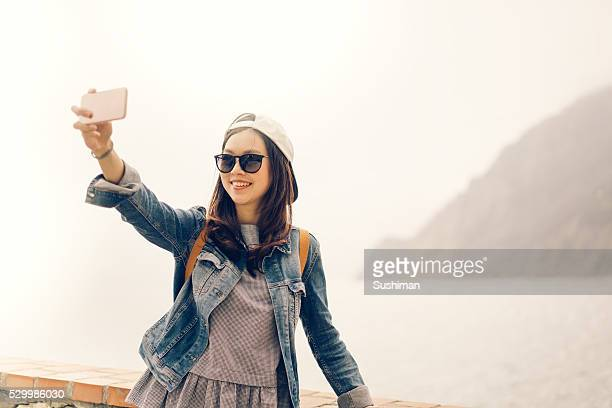 Asian traveler taking selfie with ocean view, soft warm tone
