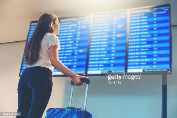 Asian Traveler women looking for flight at international airport