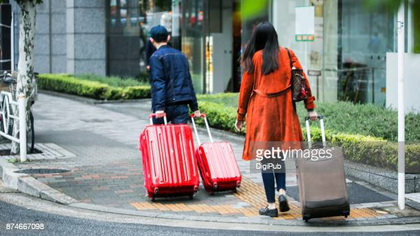 Asian travelers pulling suitcases walk on the street in Japan