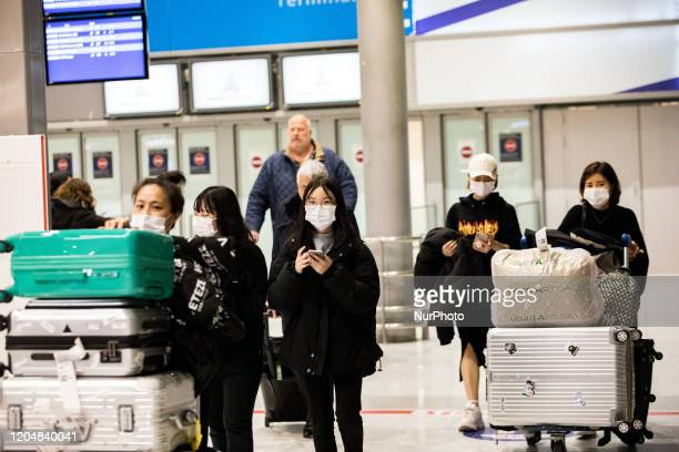 Asian travellers wear masks to avoid transmission of coronavirus upon arrival at Terminal 2 of Roissy Charles de Gaulle Airport in Roissy France on...