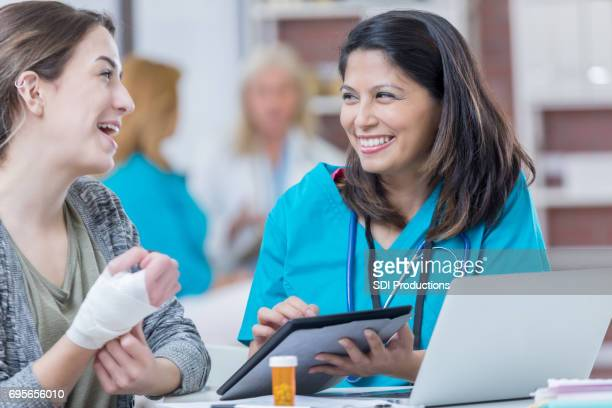 asian triage nurse uses a tablet while talking with female patient - emergency medicine stock pictures, royalty-free photos & images