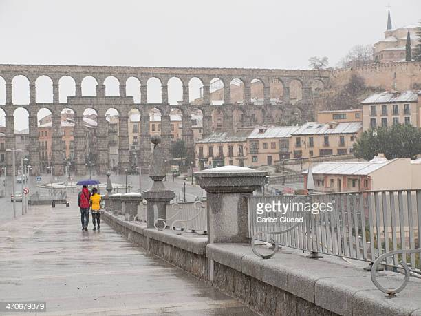 Asian turists walking under the snow in Segovia with the Aqueduct in the background. The Aqueduct of Segovia is a Roman aqueduct and one of the most...