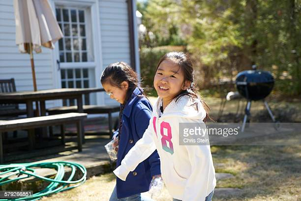 asian twin girls  playing in the backyard - scarsdale stock photos and pictures