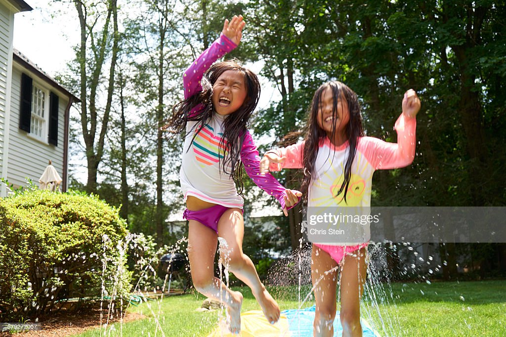 Asian Twin girls playing on slip and slide : Stock Photo