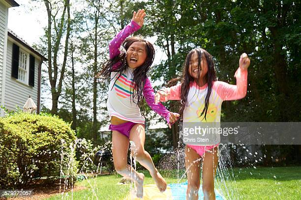 Asian Twin girls playing on slip and slide