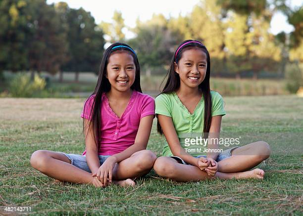 Asian twin girls smiling outdoors