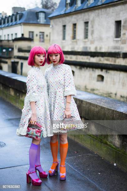 Asian twins Amiaya with pink hair wearing white dress seen outside Valentino during Paris Fashion Week Womenswear Fall/Winter 2018/2019 on March 4...