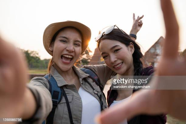 asian two young woman taking a selfie at temple in ayutthaya, thailand - tourist recording while sightseeing in asia. - thai ethnicity stock pictures, royalty-free photos & images