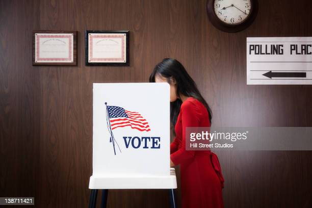 asian voter voting in polling place - votes for women stock photos and pictures